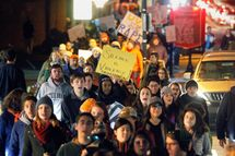 Protestors carry signs and chant slogans as they march along University Avenue on The Corner, a popular nighttime destination with bars and restaurants adjacent to the University of Virginia, Saturday night, Nov. 22, 2014, in Charlottesville, Va. The protest, the most well-attended of several throughout the day, was in response to the university's reaction to an alleged sexual assault of a student revealed in a recent Rolling Stone article. (AP Photo/The Daily Progress, Ryan M. Kelly)