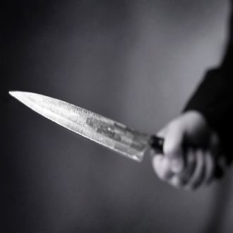 Hand wielding a menacing knife