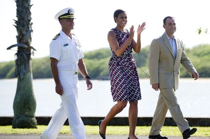 US First Lady Michelle Obama arrives to speak at a hiring fair sponsored by the US Chamber of Commerce for active and retired members of the US military and their families at Hickam Air Force Base in Hawaii, on November 14, 2011. Walking alongside Obama are Kevin Schmiegel (R), vice president of veterans employment programs at the US Chamber of Commerce, and Navy Captain Jeffrey James, commander of Joint Base Pearl Harbor-Hickam. AFP PHOTO / Saul LOEB (Photo credit should read SAUL LOEB/AFP/Getty Images)