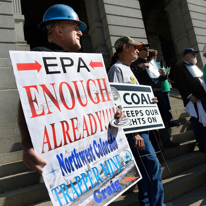 Paul Knez, left, of Craig, CO shows his support during the Enough Already Rally for Affordable Energy and Rural Communities at the State Capitol Building in Denver, CO October 30, 2013. Knez said he drives a coal haul truck at the Trapper Mine in Craig and he is concerned for his community,