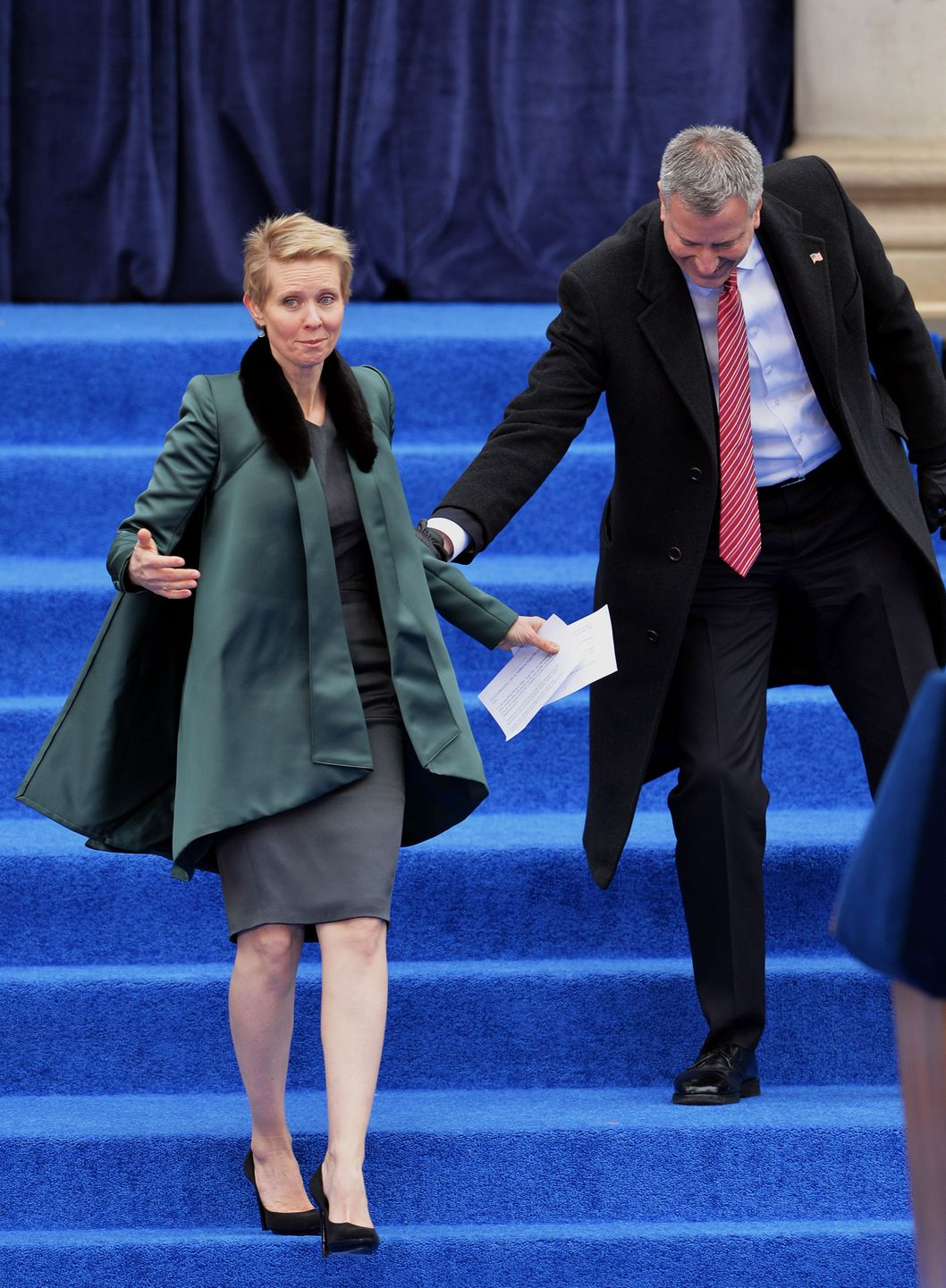 Actress Cynthia Nixon (L) is helped by New York City Mayor Bill de Blasio (R) during the inauguration on the steps of City Hall in Lower Manhattan January 1, 2014 in New Yorks. AFP PHOTO/Stan HONDA        (Photo credit should read STAN HONDA/AFP/Getty Images)