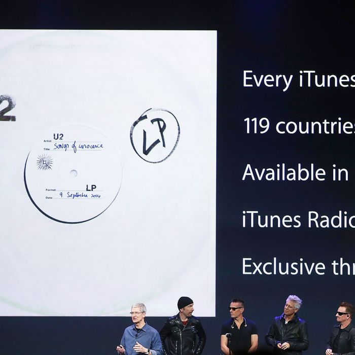 CUPERTINO, CA - SEPTEMBER 09: Apple CEO Tim Cook (L) announces the free download of the new U2 album on iTunes as members of U2 The Edge (2nd L), Larry Mullen Jr (C), Adam Clayton (2nd R) and Bono as and look on during an Apple special event at the Flint Center for the Performing Arts on September 9, 2014 in Cupertino, California. Apple unveiled the Apple Watch wearable tech and two new iPhones, the iPhone 6 and iPhone 6 Plus. (Photo by Justin Sullivan/Getty Images)