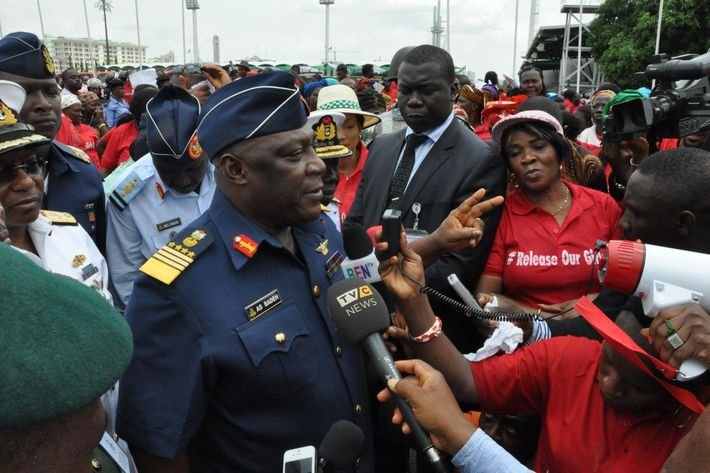 """Nigeria's chief of defense staff Air Marshal Alex S. Badeh, centre, speaks during a demonstration calling on the government to rescue the kidnapped girls of the government secondary school in Chibok, in Abuja, Nigeria, Monday, May 26, 2014. Scores of protesters chanting """"Bring Back Our Girls"""" marched in the Nigerian capital Monday to protest the abductions of more than 300 schoolgirls by Boko Haram, the government's failure to rescue them and the killings of scores of teachers by Islamic extremists in recent years. (AP Photo/Gbenga Olamikan)"""