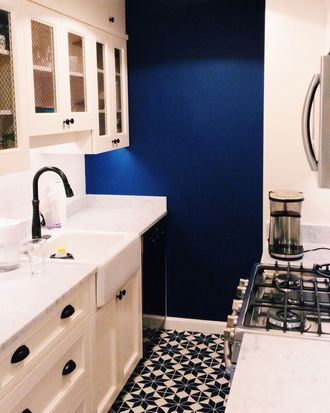 "The East Village apartment's eat-in kitchen is painted in Benjamin Moore's ""Down Pour Blue."""