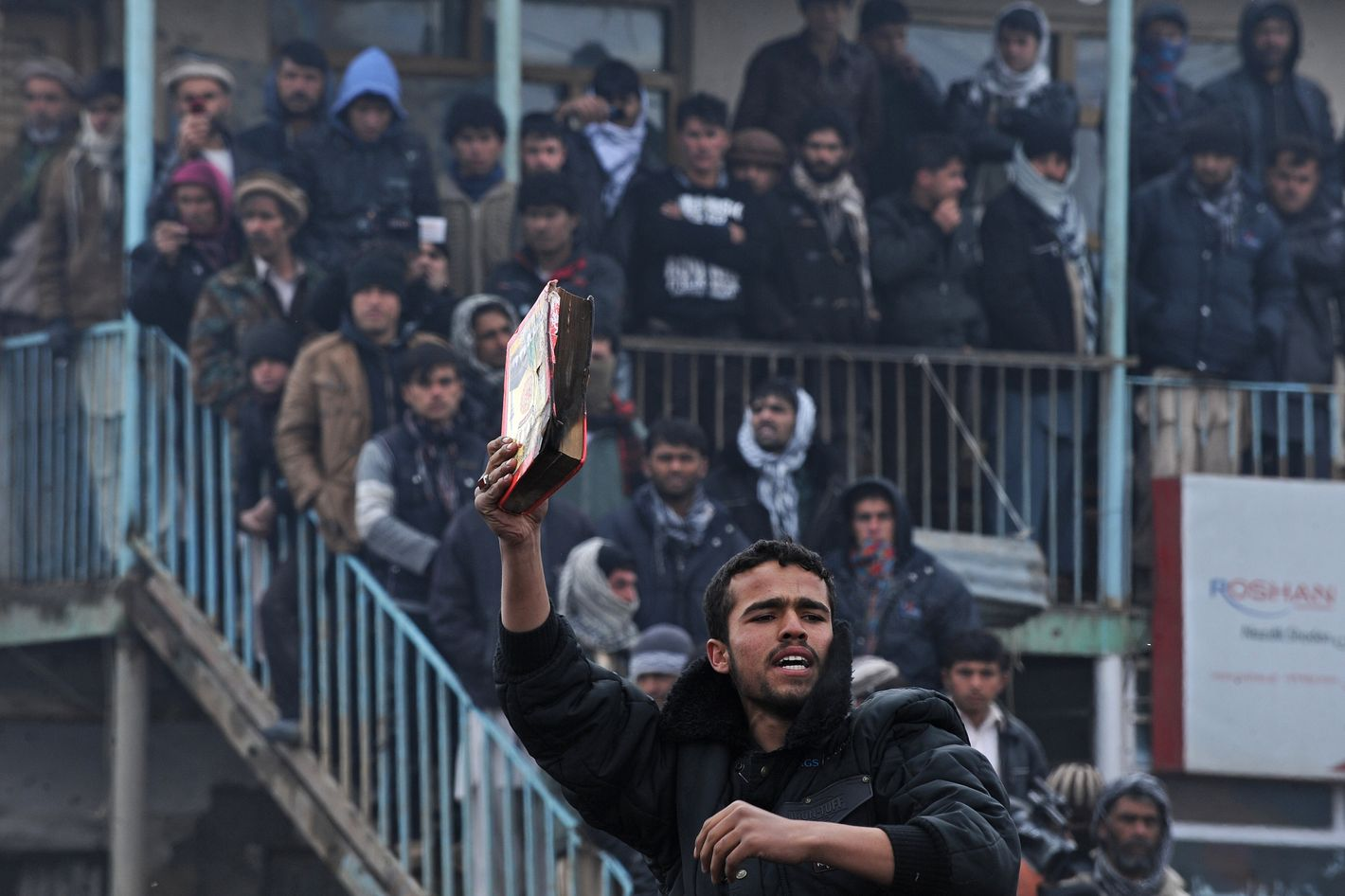 An Afghan demonstrator holds a copy of a half-burnt Koran, allegedly set on fire by US soldiers, at the gate of Bagram airbase during a protest against Koran desecration at Bagram, about 60 kilometres (40 miles) north of Kabul, on February 21, 2012.