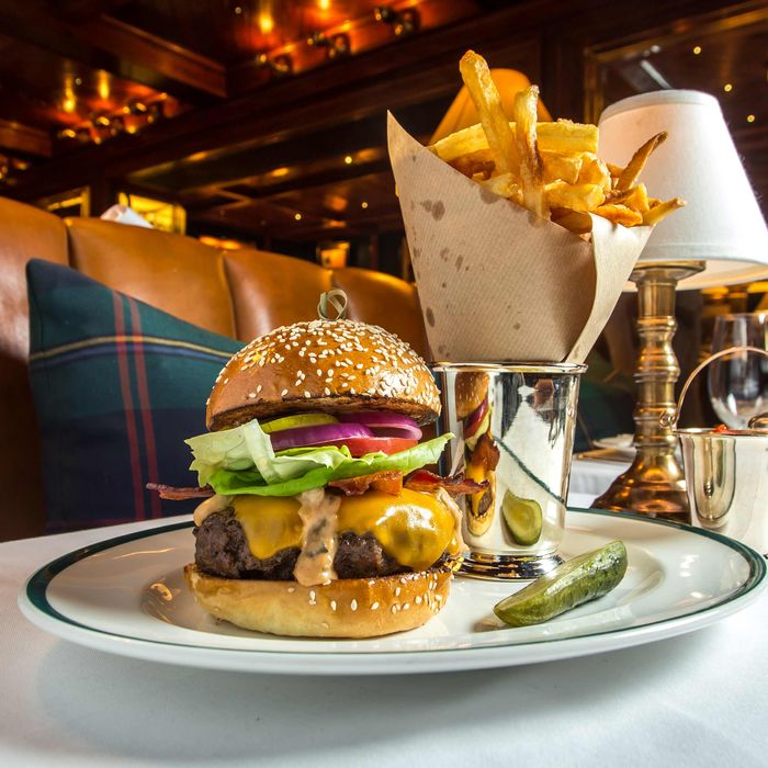 The Polo Bar Burger with tomatoes, lettuce, pickles, onions, cheddar, and crispy bacon.