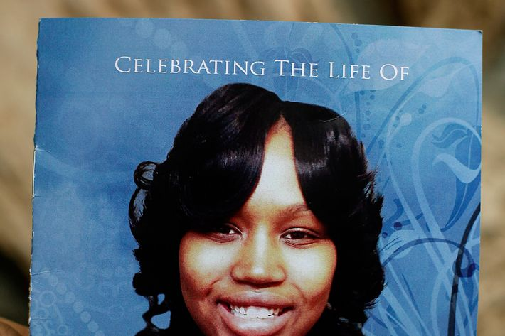 A mourner holds an obituary showing a picture of 19-year-old shooting victim Renisha McBride during her funeral service in Detroit, Michigan November 8, 2013. McBride was shot dead on November 2 at a home where she sought help after a car accident in Dearborn Heights, Michigan.