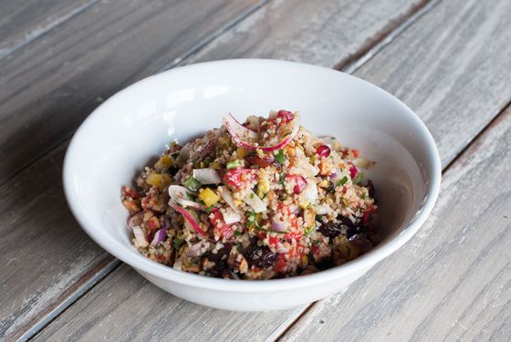 Cypriot salad with cracked bulgur wheat, smoked almond, pistachio, Medjool date, pomegranate, peppers, onion, cucumber, and cilantro.