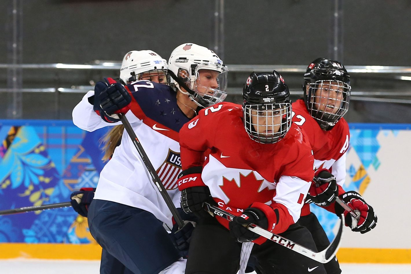 Meghan Agosta-Marciano #2 of Canada handles the puck against Lee Stecklein #2 of the United States in the second period during the Women's Ice Hockey Preliminary Round Group A game on day five of the Sochi 2014 Winter Olympics at Shayba Arena on February 12, 2014 in Sochi, Russia.