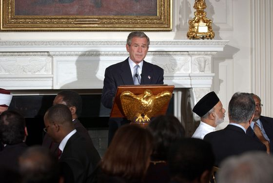 U.S. President George W. Bush (C) speaks at an Iftaar dinner hosted in the State Dining Room at the White House on November 10, 2004 in Washington, DC. The Iftaar Dinner ends the daily fast during the Muslim holy month of Ramadan.