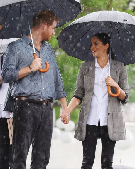 Prince Harry and Meghan Markle under an umbrella in Australia.