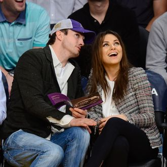 Ashton Kutcher (L) and Mila Kunis attend basketball games between the New Orleans Pelicans and the Los Angeles Lakers at Staples Center on March 4, 2014 in Los Angeles, California.