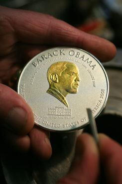 "BIRMINGHAM, UNITED KINGDOM - NOVEMBER 05:  In this photo illustration a craftsmen puts the finishing touches to a limited edition commerative coin depicting US President elect Barack Obama sits in the workshop of a die makers on November 5, 2008, in Birmingham, England. The coin has been struck to mark the historic election of Barack Obama in the United States. Birmingham company Winston Elizabeth & Windsor in association with UK Fine Arts has already sold more than 300 limited edition commemorative silver coins with solid gold versions in production. The coins depict Senator Obama's face, along with a picture of the White House and the legend ""President of the United States of America"".  (Photo illustration by Christopher Furlong/Getty Images)"