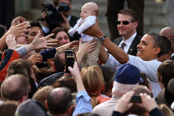 U.S. President Barack Obama lifts a baby handed to him from a supporter during a campaign rally at Elm Street Middle School October 27, 2012 in Nashua, New Hampshire. With ten days before the presidential election, Obama and his opponent, former Massachusetts Gov. Mitt Romney are criss-crossing the country from one swing state to the next in an attempt to sway voters.