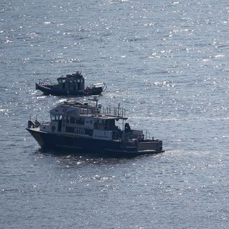 NYPD divers ride a boat on the Hudson River near the site of small plane crash, Saturday, May 28, 2016, in North Bergen, N.J. A World War II vintage P-47 Thunderbolt aircraft crashed into the river Friday, May 27 killing its pilot. (AP Photo/Julio Cortez)