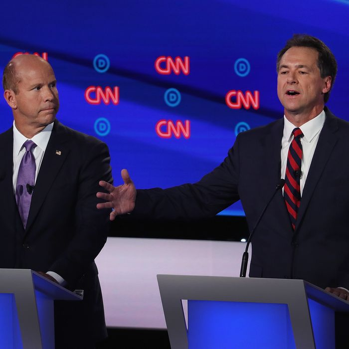 Democratic presidential candidate Montana Gov. Steve Bullock (R) speaks while former Maryland congressman John Delaney listens during the Democratic Presidential Debate at the Fox Theatre July 30, 2019 in Detroit, Michigan.