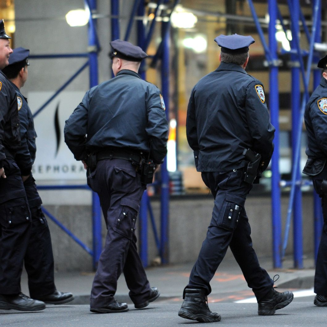 New York Police Department officers walk along a street in Lower Manhattan March 18, 2012 in New York.