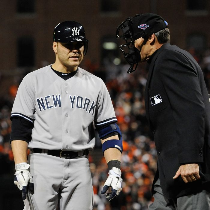 Russell Martin #55 of the New York Yankees argues with home plate umpire Angel Hernandez after striking out in the eighth inning of Game Two of the American League Division Series against the Baltimore Orioles at Oriole Park at Camden Yards on October 8, 2012 in Baltimore, Maryland.