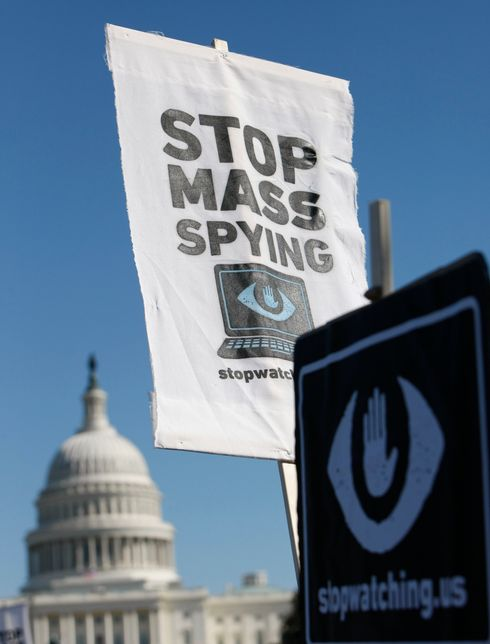 Demonstrators hold placards supporting former US intelligence analyst Edward Snowden during a protest against government surveillance on October 26, 2013 in Washington, DC. The disclosures of widespread surveillance by the US National Security Agency of US allies has caused an international uproar, with leaders in Europe and Latin America demanding an accounting from the United States.