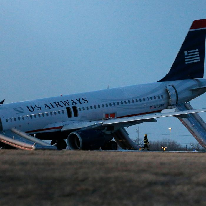 A damaged US Airways jet lies at the end of a runway at the Philadelphia International Airport, Thursday, March 13, 2014, in Philadelphia. Airline officials said the flight was heading to Fort Lauderdale, Fla., when the pilot was forced to abort takeoff around 6:30 p.m., after the front landing gear failed. An airport spokeswoman said no injuries have been reported. (AP Photo/Matt Slocum)