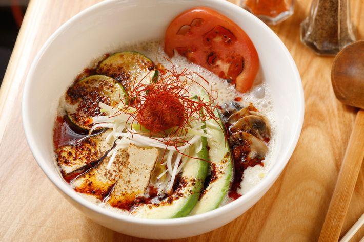 Spicy vegetarian ramen with soy milk, avocado, zucchini, tofu, mushrooms, tomato, and scallion.