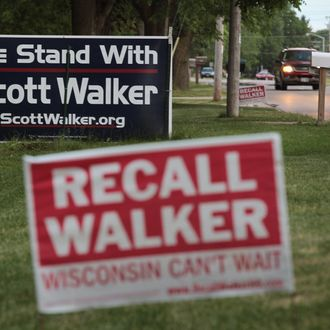 BELOIT, WI - JUNE 04: Neighbors display signs with opposite views on the Wisconsin recall election June 4, 2012 in Beloit, Wisconsin. Milwaukee Mayor Tom Barrett, a Democrat, is trying to unseat Republican Wisconsin Governor Scott Walker in the recall election scheduled for tomorrow. Opponents of Walker forced a recall election after the governor pushed to change the collective bargaining process for public employees in the state. (Photo by Scott Olson/Getty Images)