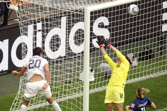 USA's striker Abby Wambach (L) heads the ball past France's goalkeeper Berangere Sapowicz to hit the crossbar during the FIFA women's football World Cup semi final match France vs USA in Moenchengladbach, western Germany, on July 12, 2011. AFP PHOTO / ODD ANDERSEN (Photo credit should read ODD ANDERSEN/AFP/Getty Images)