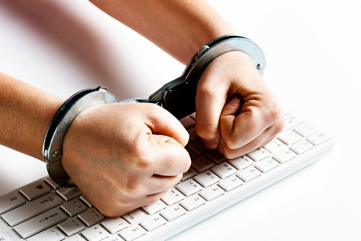 Handcuffed fists hit computer keyboard in frustration