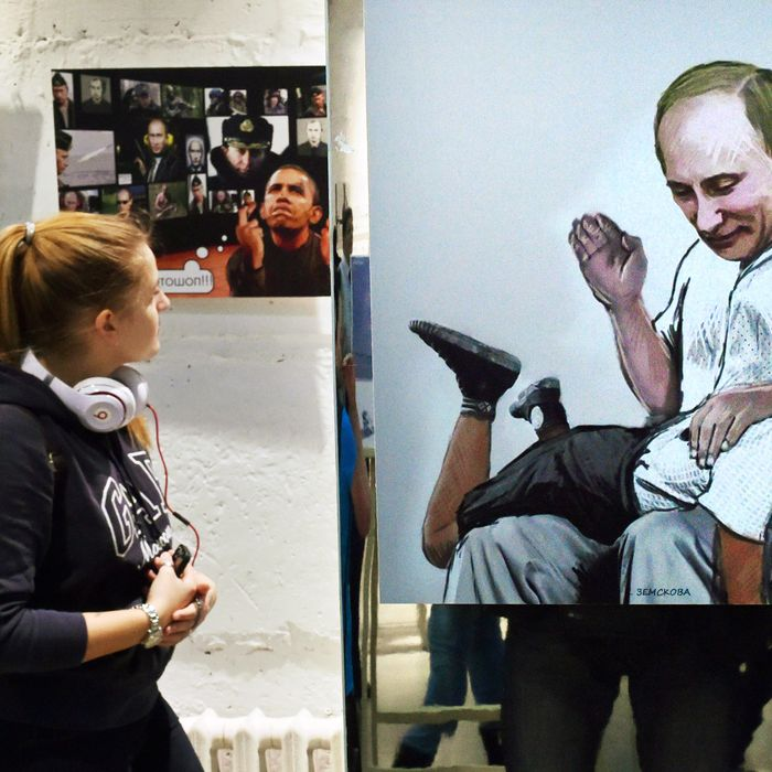 A woman looks at a cartoon displaying Russia's President Vladimir Putin and US President Barack Obama during the opening ceremony of political cartoons exhibition