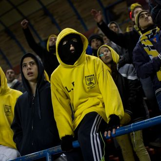 In this Tuesday, Jan. 29, 2013 photo Beitar Jerusalem F.C. soccer supporters watch a State Cup soccer match against Maccabi Umm al-Fahm F.C. at the Teddy Stadium in Jerusalem. Beitar has long tried to quell a tight-knit group that calls itself