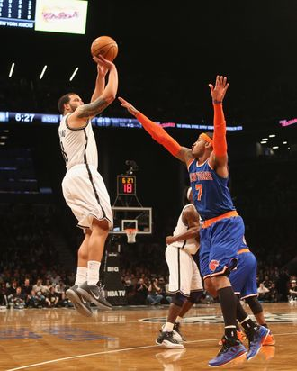 Deron Williams #8 of the Brooklyn Nets sends a shot over Carmelo Anthony #7 of the New York Knicks at the Barclays Center on November 26, 2012 in the Brooklyn borough of New York City.