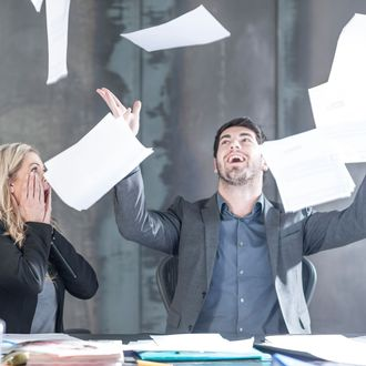 Businessman throwing papers in the air, woman looking shocked