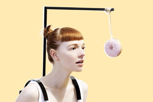 woman with donut dangling in front of face