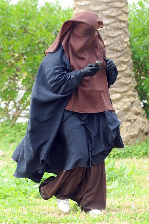 A Tunisian student wearing a niqab speeks on the phone at the Manuba university on March 7, 2012 in Tunis. Four students wearing the niqab head veil started a hunger strike on January 17, after the end of a similar hunger strike at the university which ended on January 5. Habib Kazdaghli, the Dean of the Faculty of Letters, Arts and Humanities at the University of Manuba, told an AFP journalist he would call for the dispersal of the group of Salafist students who have gathered and been involved in activities to disrupt classes and exams, their actions having caused a delay in examinations.    AFP PHOTO / FETHI BELAID (Photo credit should read FETHI BELAID/AFP/Getty Images)
