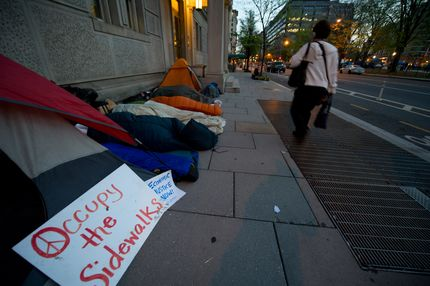 Members of Occupy DC sleep on a city sidewalk as pedestrians pass by March 26, 2012 in Washnigton, DC. The Occupiers are no longer allowed to sleep in McPherson Square, although they still maintain symbolic empty tents. AFP PHOTO/Karen BLEIER (Photo credit should read KAREN BLEIER/AFP/Getty Images)