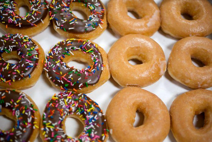 A grid of Krispy Kreme doughnuts, half chocolate sprinkle and half plain