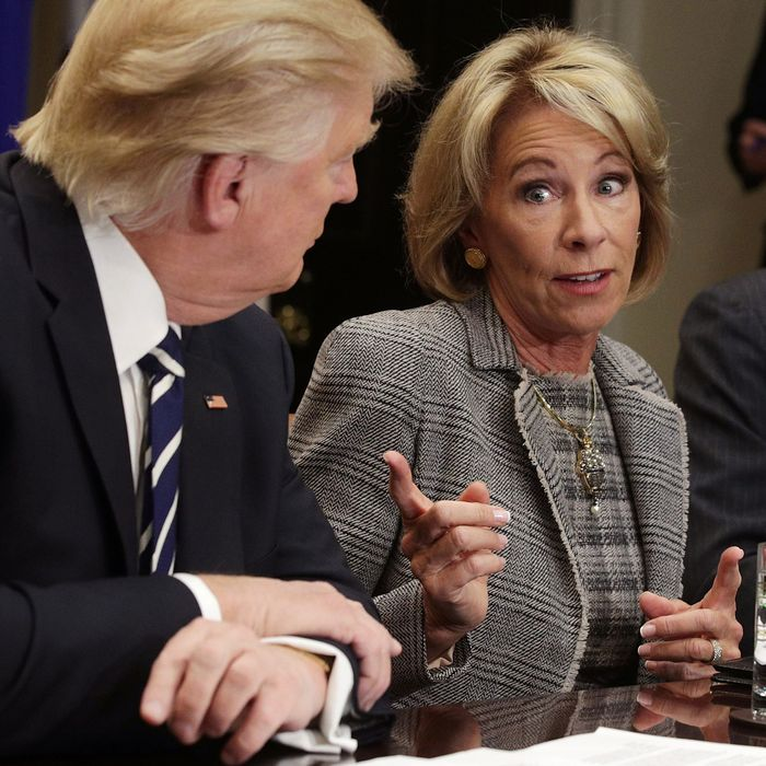 U.S. Secretary of Education Betsy DeVos speaks as President Trump listens during a parent-teacher-conference listening session.