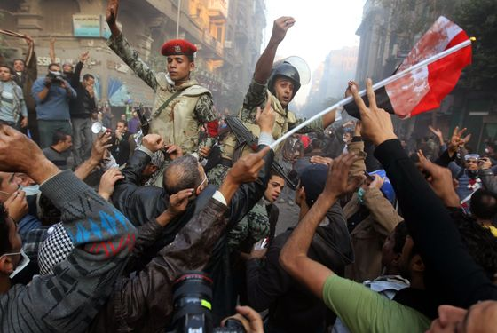 Egyptian soldiers try to keep thousands of protesters away from riot policemen during a demonstration in Cairo's landmark Tahrir Square on the fourth day of clashes with security forces on November 22, 2011, to demand an end to military rule, heightening tension after days of deadly clashes that threaten to derail next week's legislative polls.  AFP PHOTO/KHALED DESOUKI (Photo credit should read KHALED DESOUKI/AFP/Getty Images)