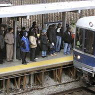 Passengers wait as the Metro-North passenger train approaches the platform 21 December, 2005 at the Fordham Rd station in the Bronx borough of New York. Metro-North offered passengers in the Bronx, who normally use subways and buses, an alternative way to get into Manhattan during the transit strike. The city's nearly 34,000 subway and bus workers stayed out for a second day on Wednesday despite a court order fining their union one million dollars per day during the stoppage.