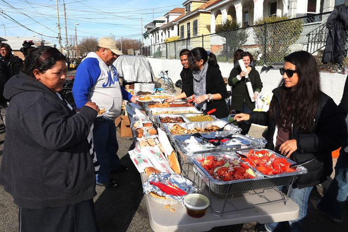Volunteers from Astoria distribute food to needy and displaced residents on Beach 24th Street on November 20, 2012 in Far Rockaway, Queens, New York. More than three weeks after Superstorm Sandy hit the New York area, residents continue their restoration efforts in many affected areas in the New York region.
