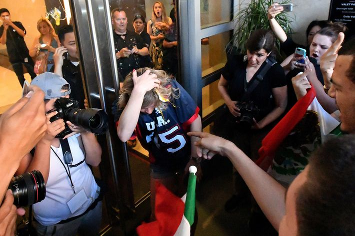 A woman wearing a Trump shirt is pelted with eggs by protesters while pinned against a door near where Republican presidential candidate Donald Trump holds a rally in San Jose, California on June 02, 2016.