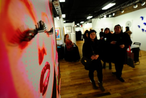 Visitors walks through the Red Dot Art Fair and the Korean Art Show, in New York, March 3, 2011. New York kicked off its annual art week with shows and art fairs throughout the  city such as The Armory Show, Fountain , Red Dot, Volta NY, and Pulse amongst others , are expected to draw more than 60,000 attendees and generate more than $40 million in economic activity in New York City. AFP PHOTO/Emmanuel Dunand (Photo credit should read EMMANUEL DUNAND/AFP/Getty Images)