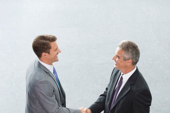 Businessmen shaking hands in office lobby