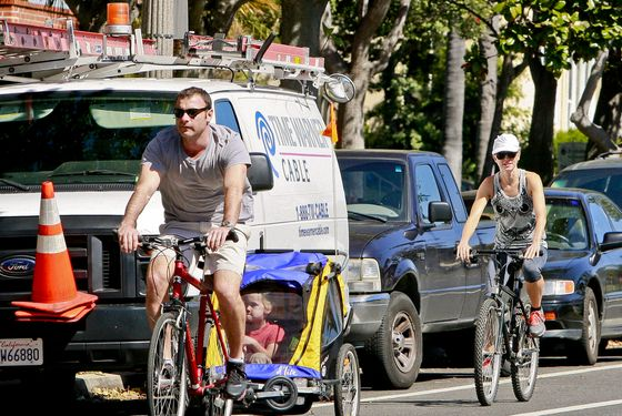 Schreiber and Watts cheating on New York bike lanes with ones in Los Angeles. (Here in New York, they wear helmets, we promise.)