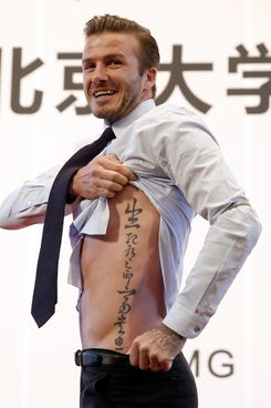British football player David Beckham shows his tattoo to fans during his visit to Peking University on March 24, 2013 in Beijing, China. David Beckham is on a five-day visit to China at the invitation of the China Football Association as China's first international ambassador.