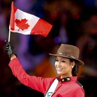Kesiah Papasin of Canada waves a Canadian national flag as she poses in a costume during the 54th Miss International Beauty Pageant in Tokyo
