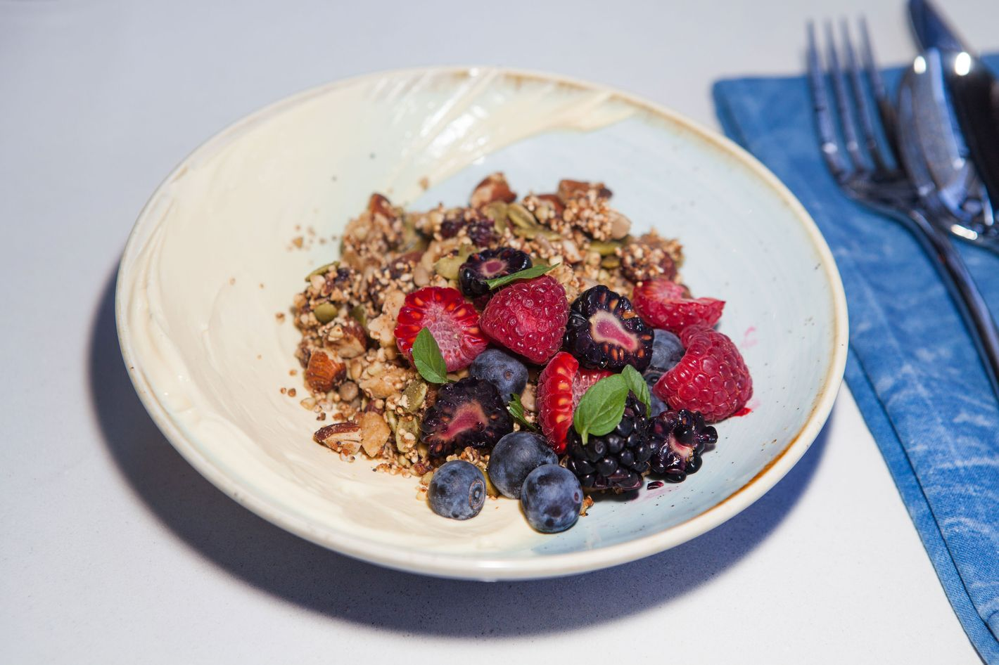 Housemade granola with passion-fruit yogurt and berries.