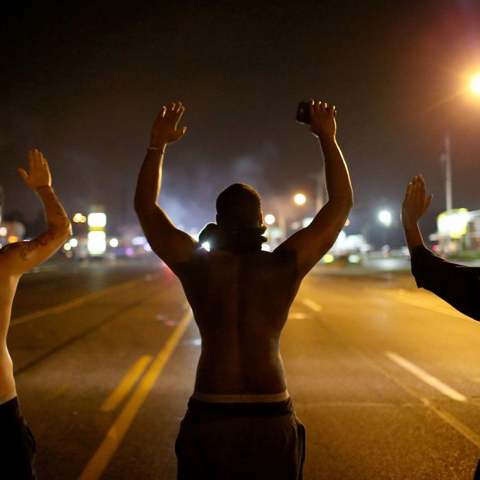 "Demonstrators raise their arms and chant, ""Hands up, Don't Shoot"", as police clear them from the street as they protest the shooting death of Michael Brown on August 17, 2014 in Ferguson, Missouri."