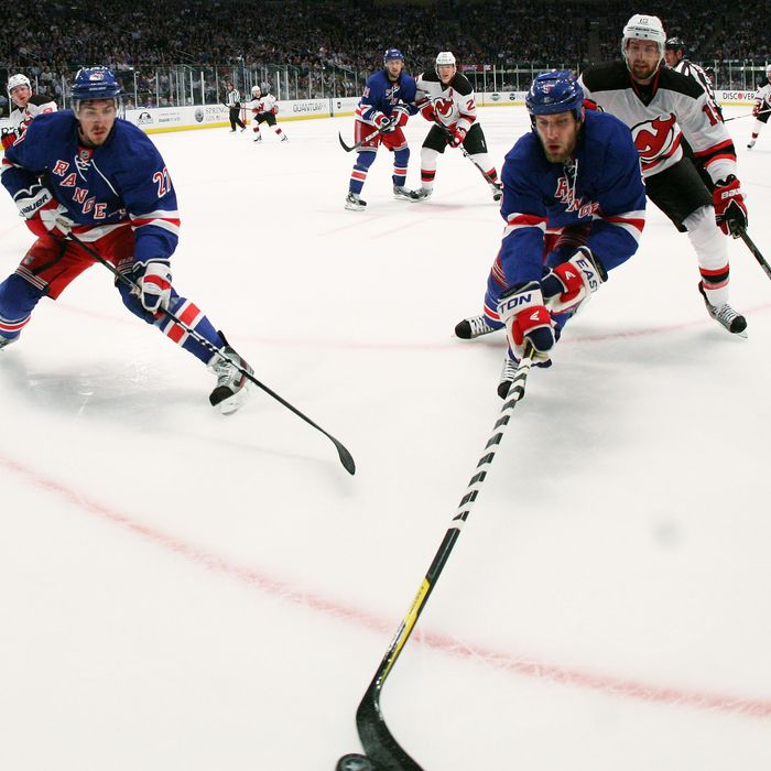 Dan Girardi #5 of the New York Rangers controls the puck against Travis Zajac #19 of the New Jersey Devils