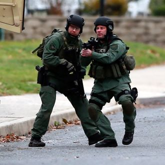 Police move near the scene of a shooting Monday, Dec. 15, 2014, in Souderton, Pa. Police are surrounding a home in Souderton, outside Philadelphia, where a suspect is believed to have barricaded himself after shootings at multiple homes. Police tell WPVI-TV the man is suspected of killing a five people Monday morning at three different homes northwest of Philadelphia.